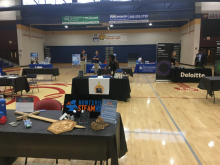 Picture of tables set up by employers at job fair in the gym at Columbia High School