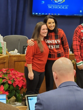 Columbia teacher Karli LeCompte pictured in red with Huntsville City School's Superintendent after being recognized for receiving National Boards in Mertz Board Room