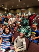 4th Grade students posing for a picture with Lady Liberty at the assembly wearing green Lady Liberty hats.