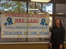 """Mrs. Lang and her banner, which reads, """"Congratulations Mrs. Lang Challenger Elementary's Teacher of the Year,"""" in the lobby of Challenger Elementary"""