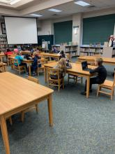 Students sitting in library at tables with computers coding for Hour of Code
