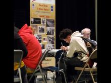 Two students in a red sweatshirt and one in a white sweatshirt sitting at table participating in a Mock Election sponsored by the Alabama League of Women Voters