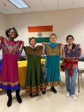 CMS students holding up authentic Indian dresses