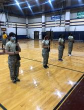 Cadets in the school's gym holding rifles up during practice at Operation Quick Start