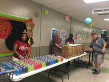 Teachers prepare to serve pizza to the students
