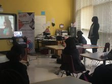 Representative from Pathway 2 Success standing in front of window and girls sitting at table watching video in classroom