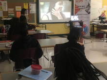 Presenter standing in front a group of Columbia girls showing a video about Pathway 2 Success program