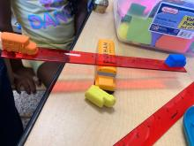 Pre-K Sensory items, orange, blue, yellow bus balanced on a ruler