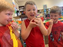 Three Pre-K students eating tomatoes from their garden