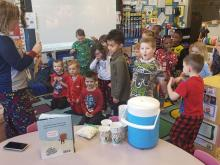 Mrs. Harbour and PreK students standing in classroom reading a clue from the gingerbread packet