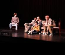 actors on a couch on stage