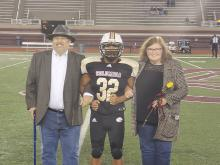 Football player poses on the football field with parents during senor night at  Columbia High School