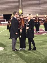 A member of the band pictured with his parents on the football field posing during senior night at Columbia High School