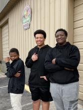 Three students standing outside of the Manna House in Huntsville after Volunteering