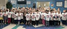 2nd grade students in lobby of school wearing their Liberty Legacy tshirts with Ms. Hill holding her super citizen award