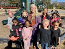 Susan Lewis, Blossomwood's Teacher of the Year, poses on the playground with some of her students.