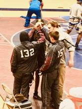 3 students in brown uniforms huddled with wrestling coach Mcrea on floor before wrestling match