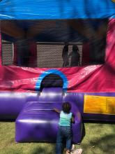 Two students bouncing in a bounce house and one sibling crawling into the bounce house