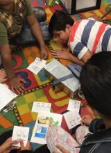 Students on rug working on the puzzle portion of the math quest
