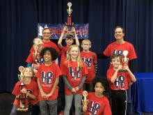 Blossomwood Chess Club members hold up the trophies they won at the Rookie Rally Tournament.