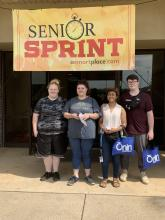 Yellow sign that says Senior Sprint with four seniors outside of Jaycees building