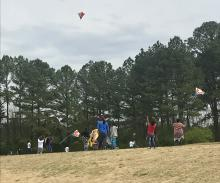 Parents and students flying kites up on the track at MLK