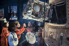 Three young children looking at a space capsule.