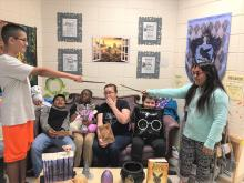 Teacher and Harry Potter Book Club sitting on a couch with 5 students  in the GATE room, two students pointing wands at each other