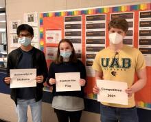 winning cyber students holding signs