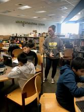 Librarian assisting 4th grade studenst with research project