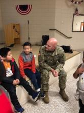 Soldier talking with 2 first grade students