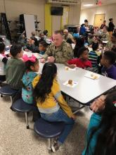 soldiers from Redstone Arsenal enjoy muffins with first graders