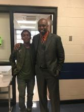 Assistant principal, Chris Sims, standing with a student in his office.