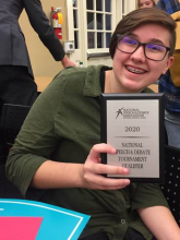 Smiling student with Speech and Debate plaque