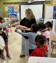 Principal Marcia Sutton receiving thank you cards from kindergarten students