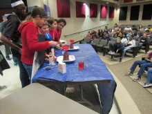 Students at Williams Middle School participating in the Baking Soda Volcano activity by pouring baking soda into the volcano.