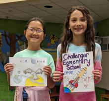 Alexia and Bella holding the covers they drew for the contest
