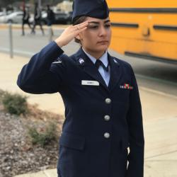 JHS AFJROTC cadet in uniform stands in a salute outside the school on Pearl Harbor Remembrance Day.