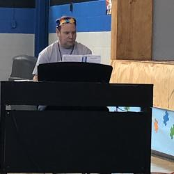 r. Thorson sporting an autism awareness bandanna while playing the piano for WMS choir singing Courage