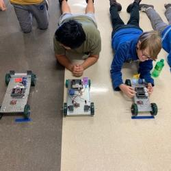 Two boys lie in the floor, preparing to launch their robot dragsters.