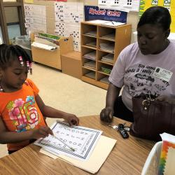 a kindergarten student identifying letters at her conference with her mother