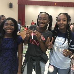 Three Williams Middle School students posing with their STEM project of a rocket.