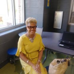 District 1 representative Michelle Watkins seated in a yellow dress