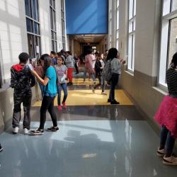 Picture of students looking in the hallway for items in scavenger hunt.
