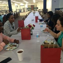 Parent volunteers of CHS students enjoying lunch at table with food and gifts
