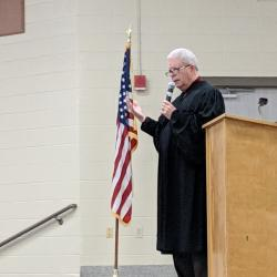 "Judge Bell standing near the podium swearing the whole school in as ""Lifelong Readers"""