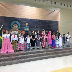 This is a fashion show held at the school. There are a lot of students dressed in beautiful clothing that represents the country