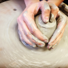 View Hands molding clay.