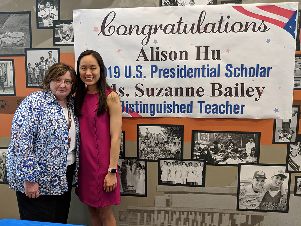 Alison Hu and Ms. Bailey in front of a sign congratulating them for being selected as Presidential Scholars Student and Teacher