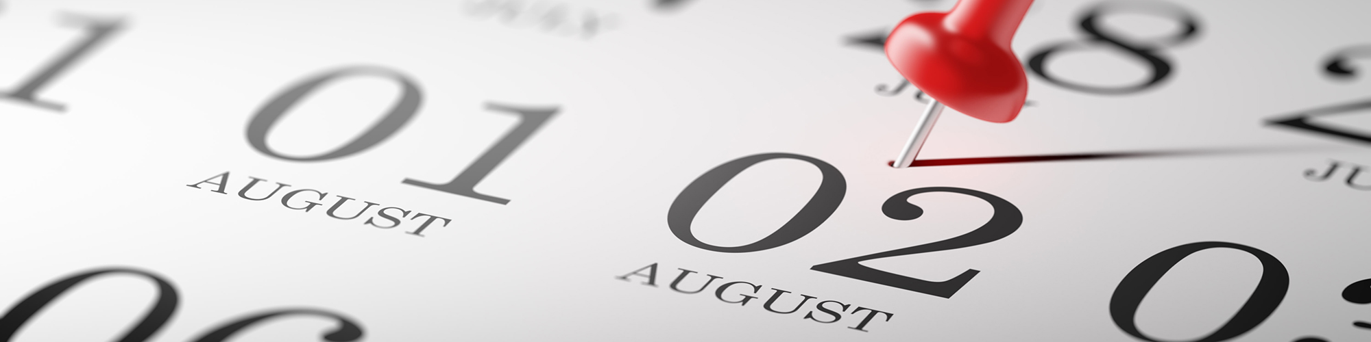 Close-up view of a calendar with a pin on August second.